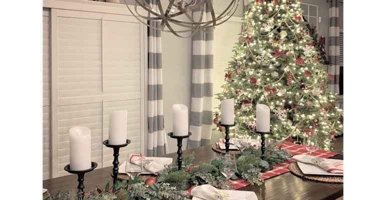 Christmas table with candles in festive dining room.