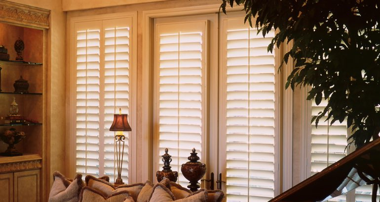 Plantation shutters on french door and window in Cincinnati parlor