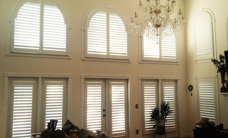 Entertainment room in two-story Cincinnati house with plantation shutters on high ceiling windows.