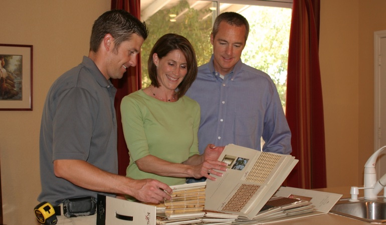 Homeowners looking at samples of window treatments.