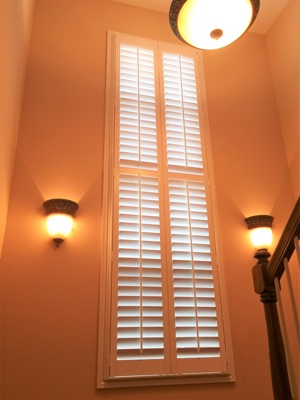 White plantation shutters in brightly lit stairwell.