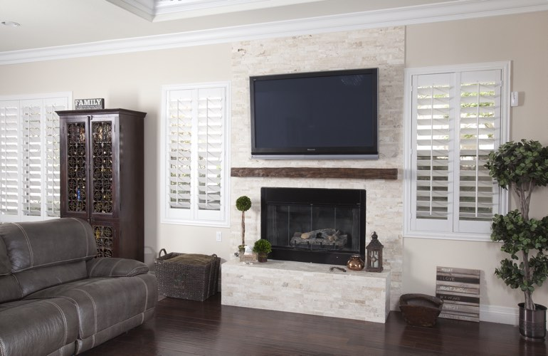 White plantation shutters in a Cincinnati living room with plank hardwood floors.