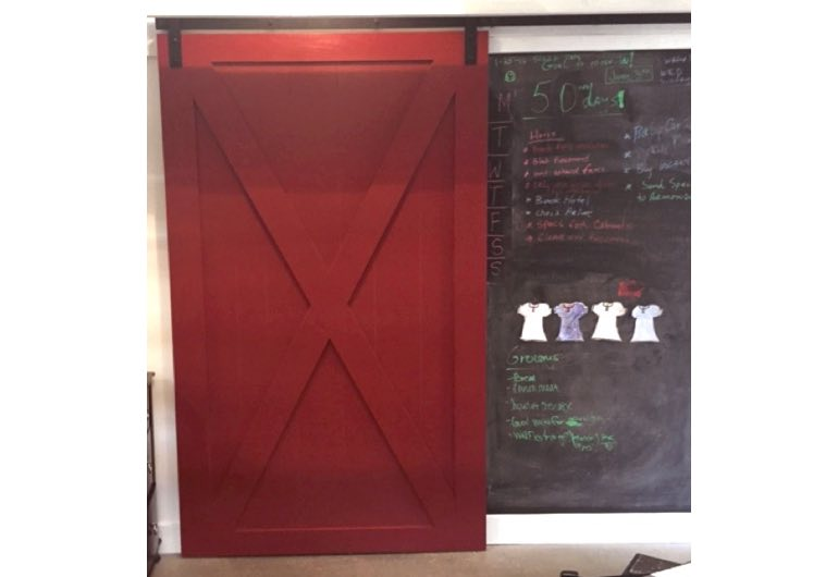 Bright red sliding barn door with black track next to chalkboard