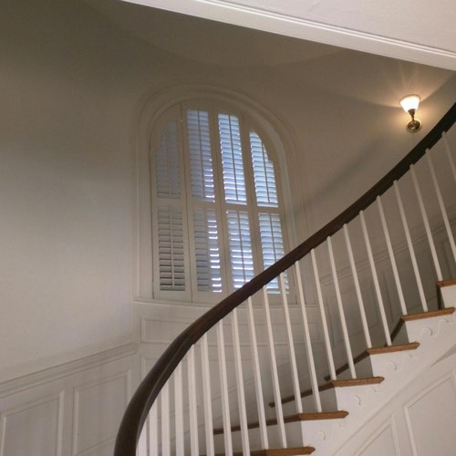 White plantation shutters covering arched window located in spiral stairwell.