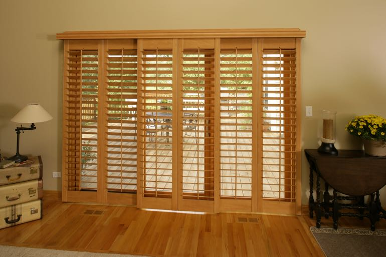 Wood shutters on sliding door leading to outdoor porch.