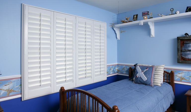 White plantation shutters in blue kids bedroom in Cincinnati